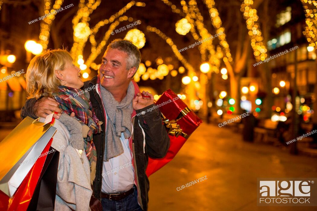 Imagen: Mature couple carrying xmas shopping on tree lined avenue, Majorca, Spain.