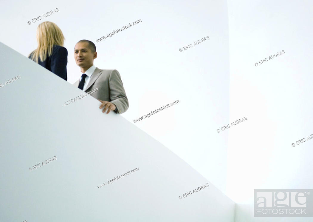 Stock Photo: Businessman and businesswoman standing face to face, low angle view.
