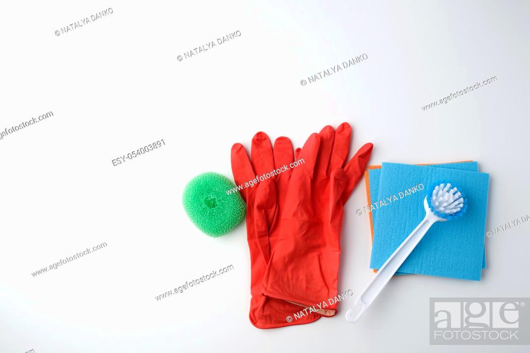 Stock Photo: items for home cleaning: red rubber gloves, brush, multi-colored sponges for dusting on a white background, top view, flat lay.