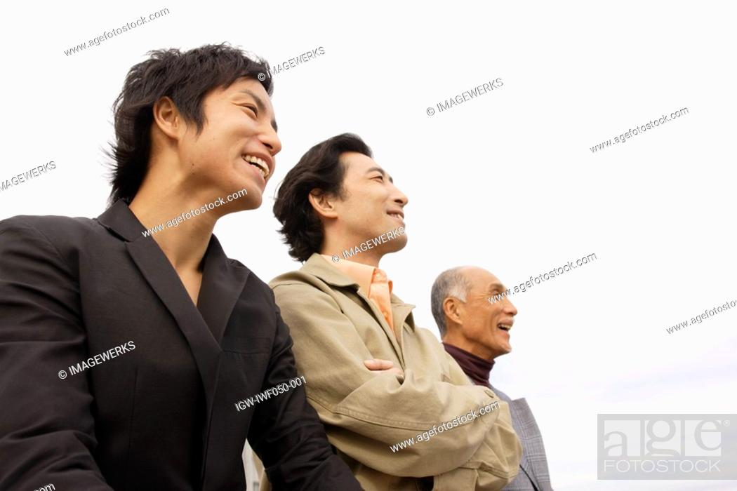 Stock Photo: Young man with father and grandfather, smiling.