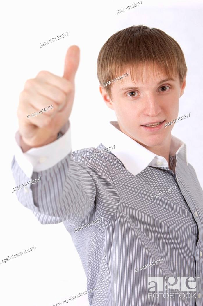Stock Photo: Young man looking at the camera and smiling with thumbs up.
