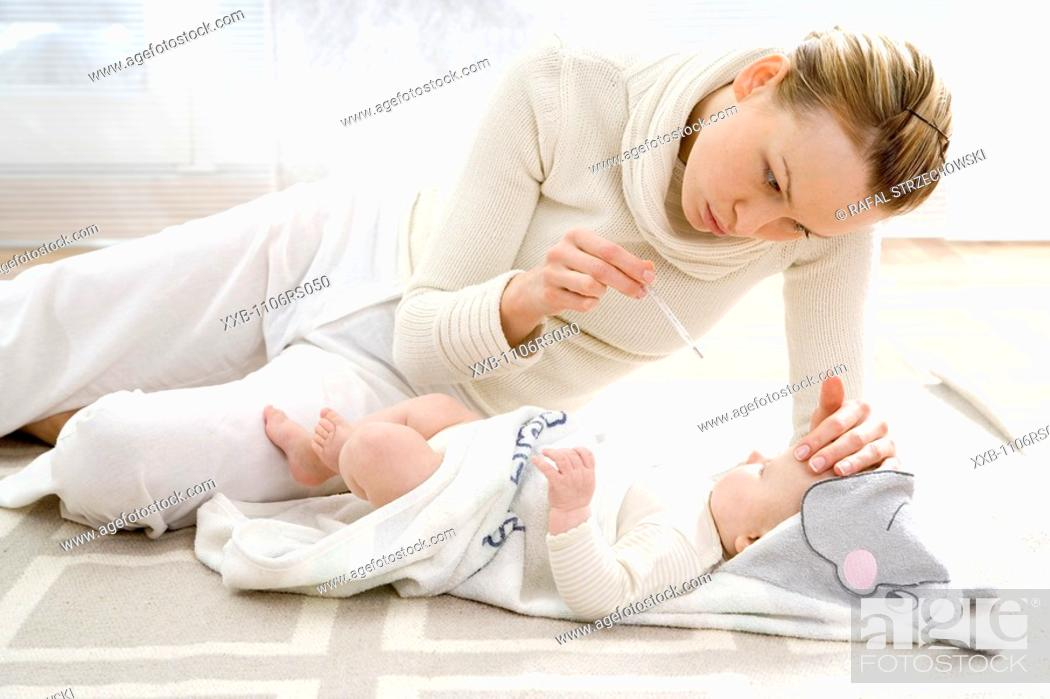 Stock Photo: mother measuring infant's temperature.