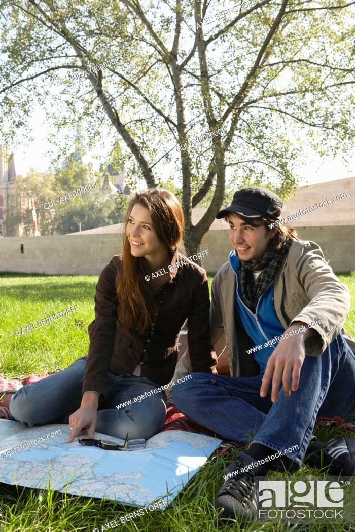 Stock Photo: Couple with a map and compass in a park smiling.
