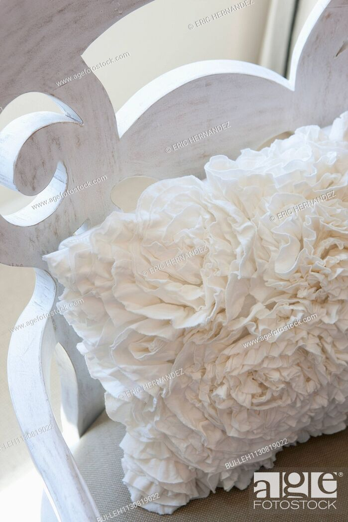 Imagen: White throw pillow on wooden chair.