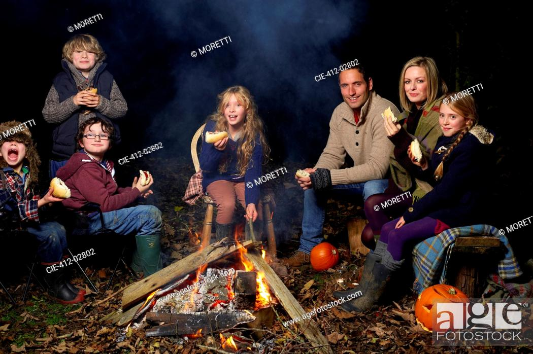 Stock Photo: Family eating around campfire at night.