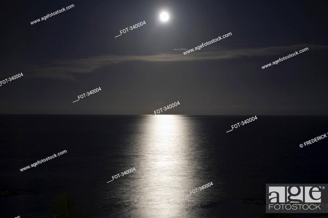 Stock Photo: Full moon reflecting on water at night.