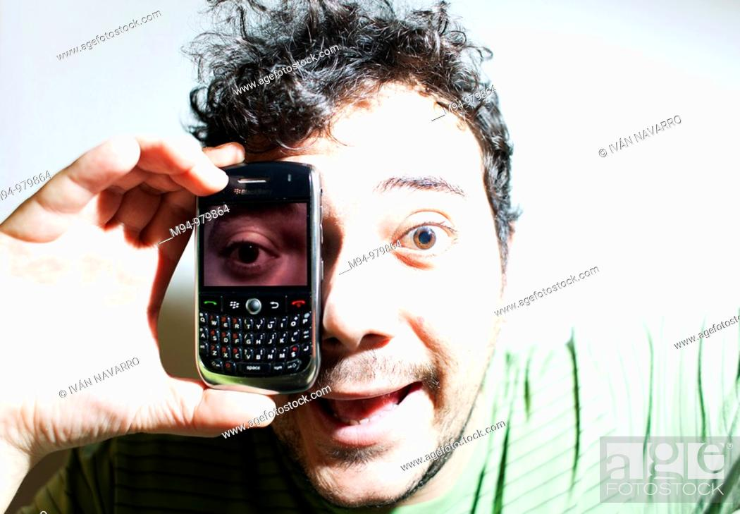 Stock Photo: Man with a mobile phone with a photography of his eye.