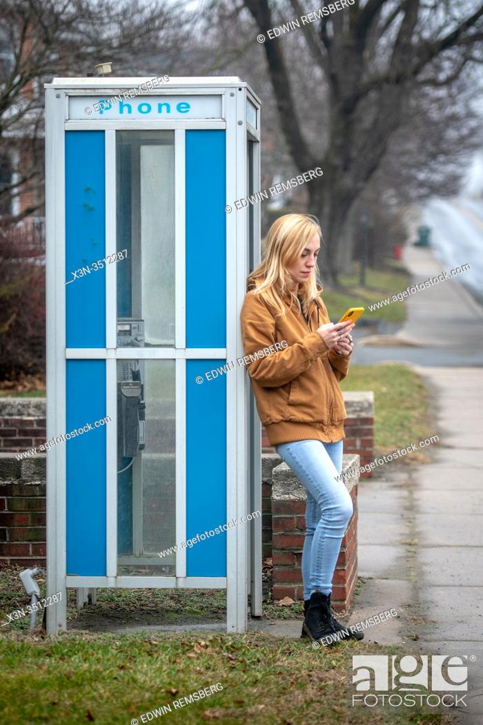 Stock Photo: A woman leaning on a phone booth checks her smart phone , Lancaster, Pennsylvania, USA.