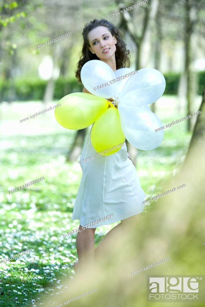 Stock Photo: Young woman walking in meadow, holding balloons, looking away.