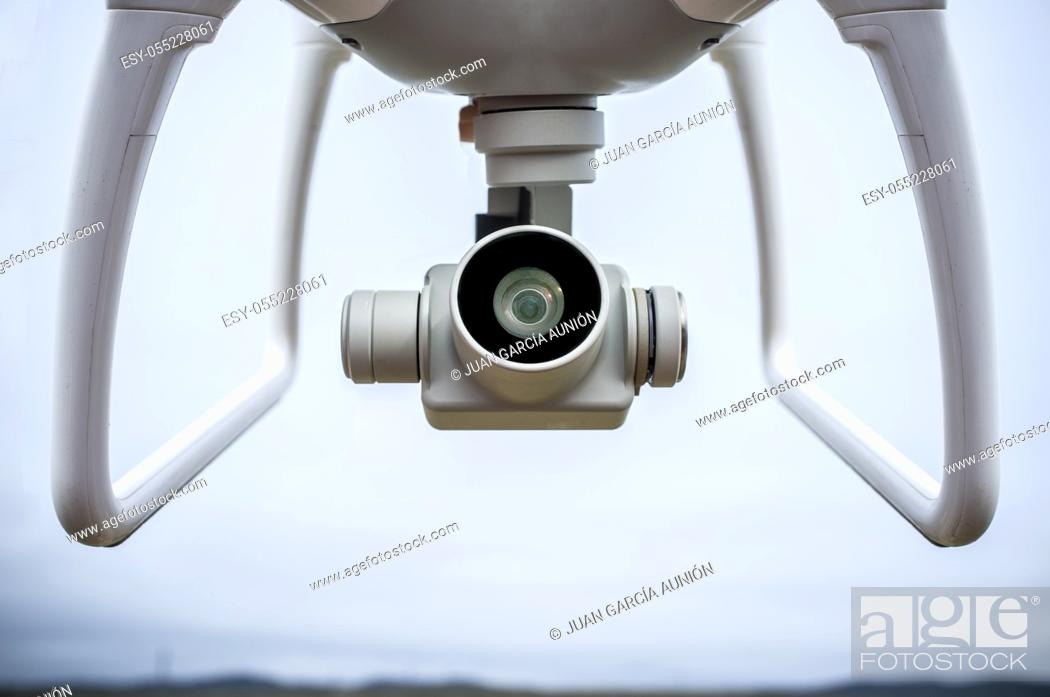 Stock Photo: Video camera with gimbal stabilizer placed between both dron legs. Closeup.