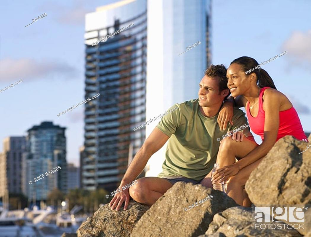 Stock Photo: USA, California, San Diego, sporty couple sitting on rock overlooking harbour, smiling, side view.