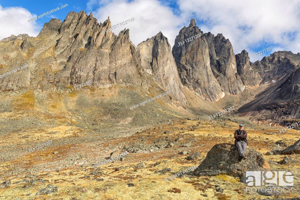 Stock Photo: Man sitting on a rock underneath the jagged granite peaks of Tombstone Territorial Park; Yukon, Canada.