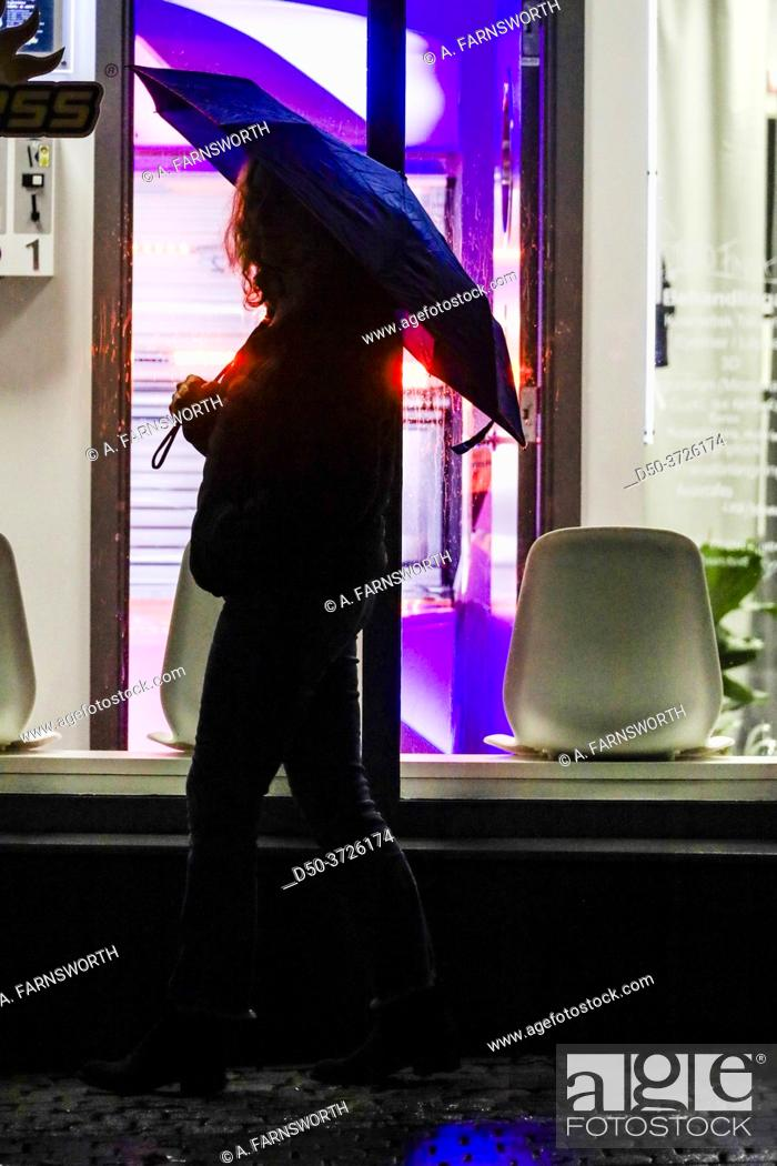 Stock Photo: Stockholm, Sweden A woman with an umbrella walks by a tanning salon in Liljeholmen at night.