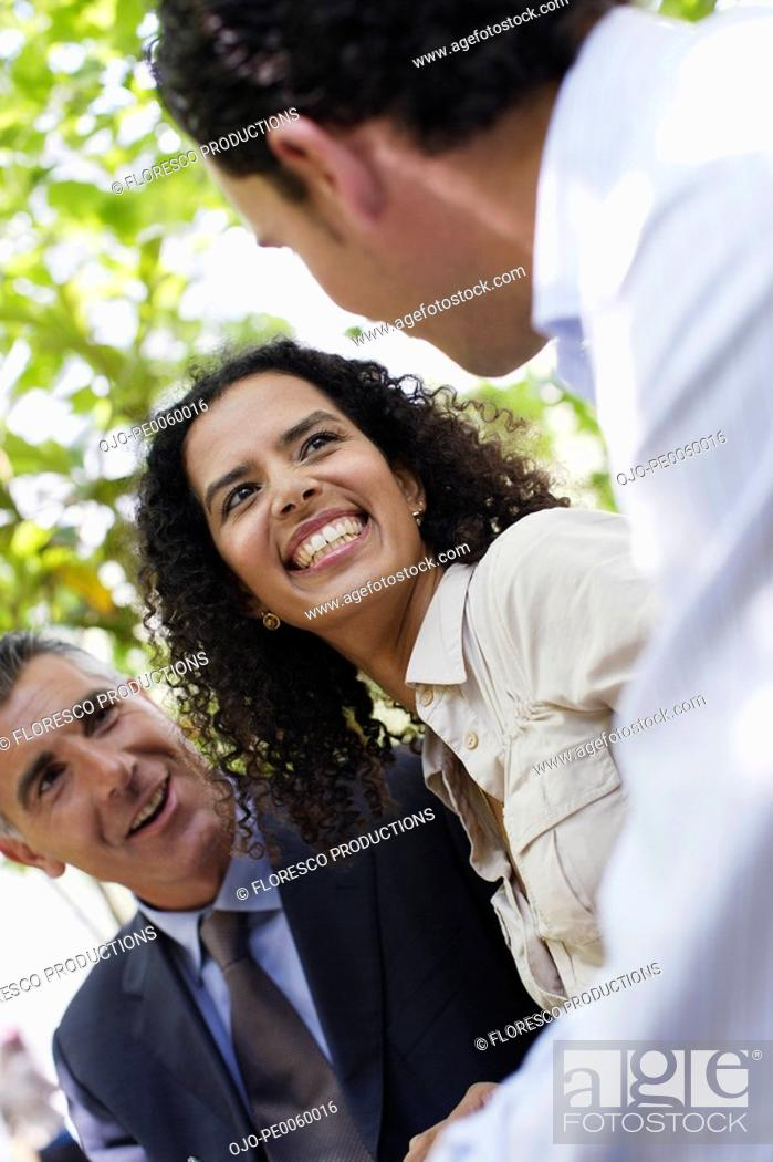 Stock Photo: Three businesspeople outdoors talking and laughing.