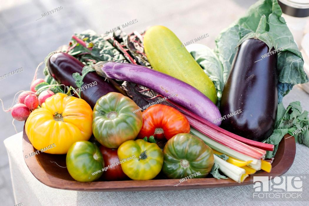 Stock Photo: Wooden bowl with fresh vegetables standing on a table.
