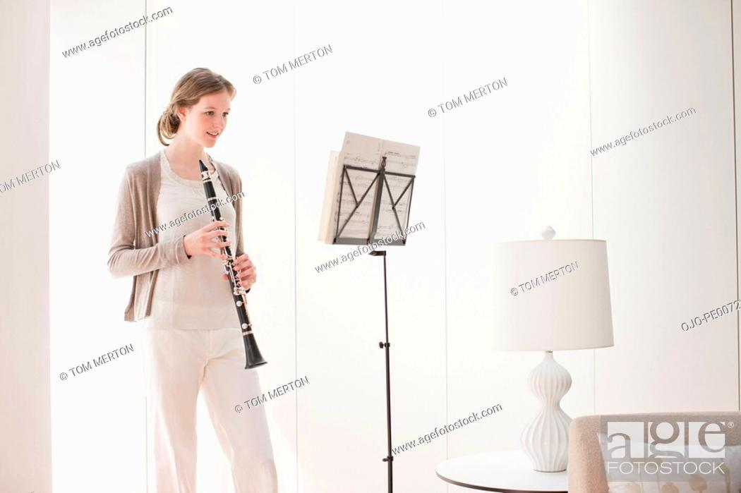 Stock Photo: Woman holding clarinet and looking at sheet music.