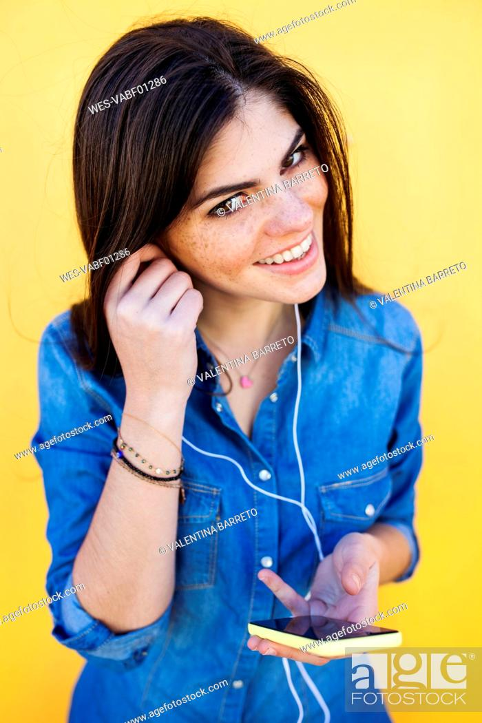 Stock Photo: Portrait of smiling young woman with earphones and smartphone in front of yellow background.