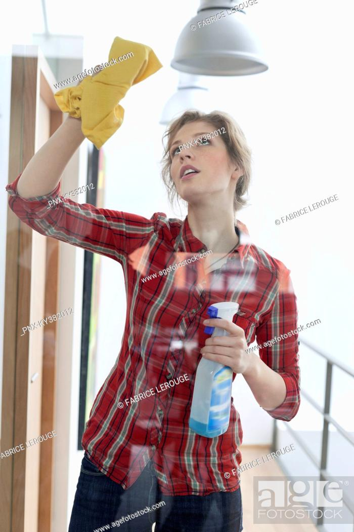 Stock Photo: Woman cleaning a glass door.