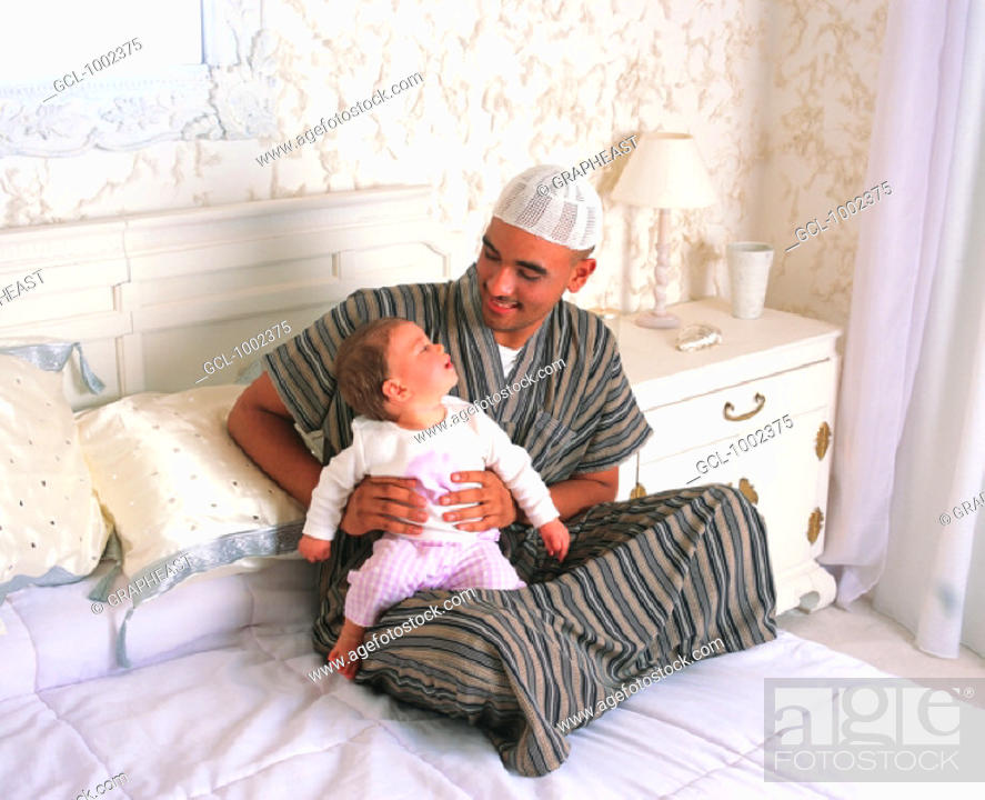 Stock Photo: Father and toddler on bed.