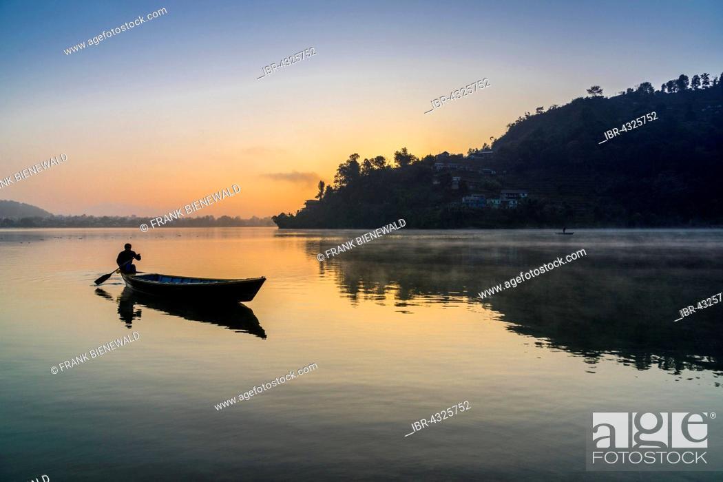 Stock Photo: Man paddling a boat across Phewa Lake at sunrise, Pokhara in the distance, fog, Anadu Palpari, Kaski, Nepal.