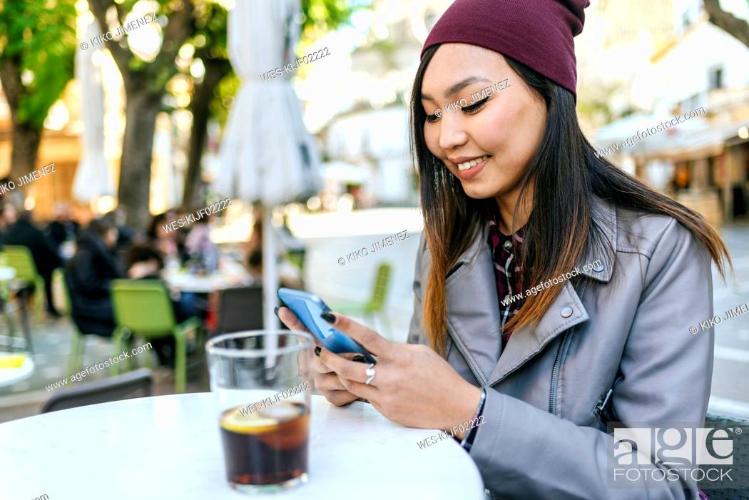 Stock Photo: Smiling young woman using smartphone at pavement cafe.