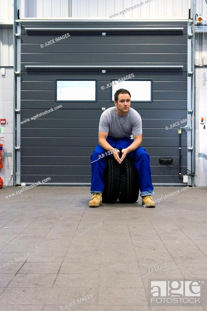 Stock Photo: Mechanic in garage on tyres, portrait, low angle view.