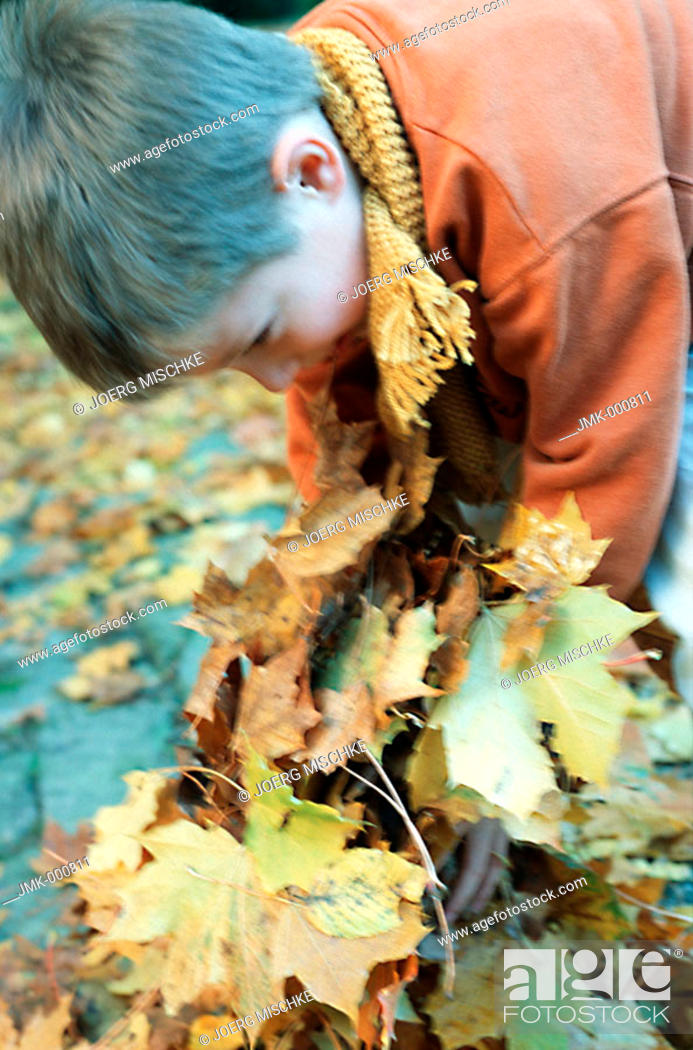 Stock Photo: Little boy in the autumnal wood, forest, playing with coloured leaves.