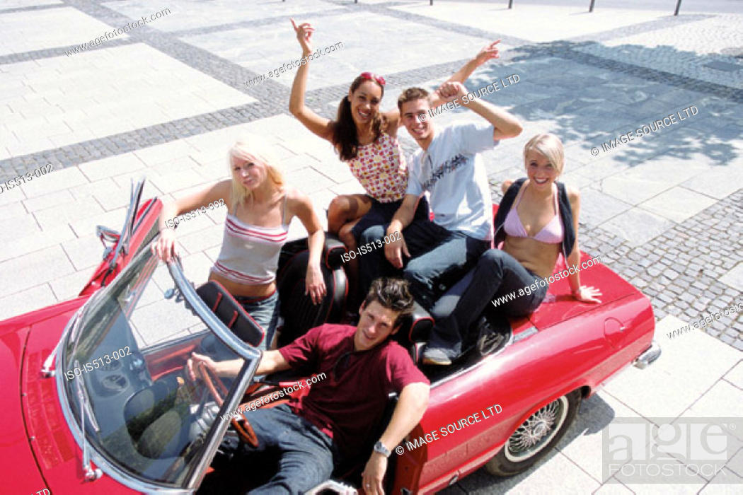 Stock Photo: Group of young friends sitting on car.