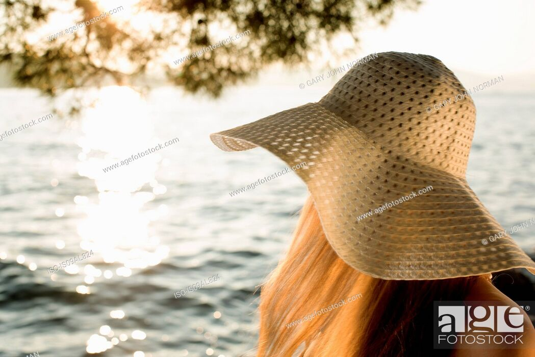 Stock Photo: Young woman in sunhat at coast, Milna, Brac, Croatia.