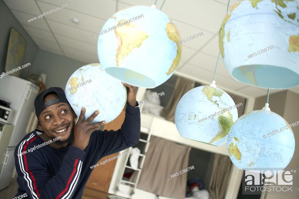 Stock Photo: optimistic African man listening to excitement of world globes.
