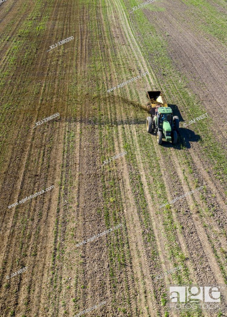 Stock Photo: Three Oaks, Michigan - Dairy farmer Howard Payne spreads manure on a field as fertilizer.