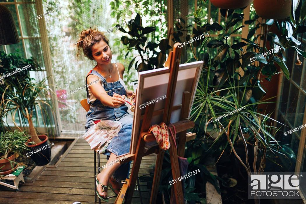 Stock Photo: Indoor shot of professional smiling female artist painting on canvas in studio with plants.