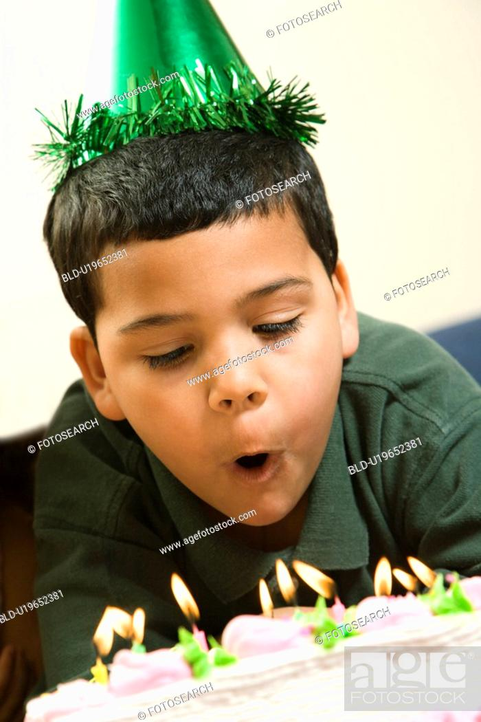 Stock Photo: Hispanic boy wearing party hat blowing out candles on birthday cake.