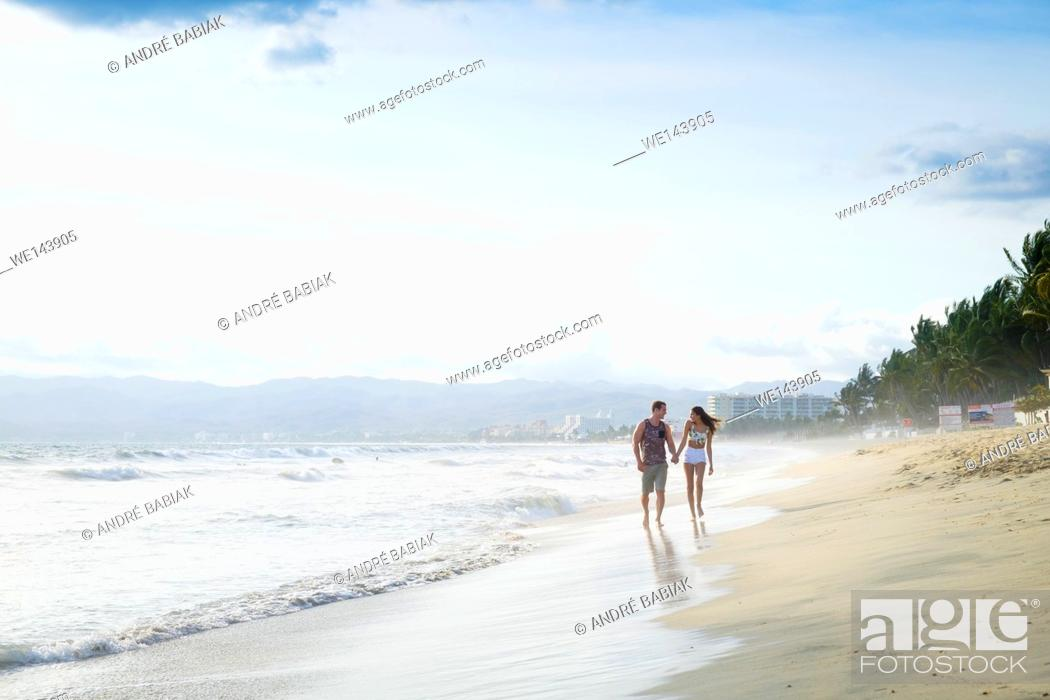 Stock Photo: Young couple walking on lonely beach - Riviera Nayarit, Mexico.