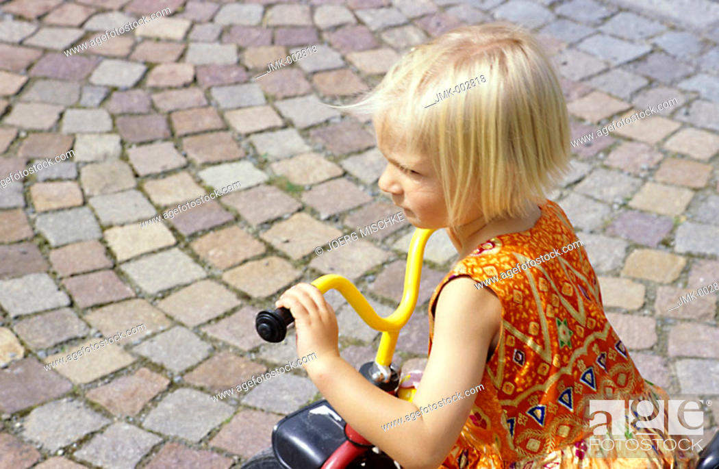 Stock Photo: A little girl, 5-10 years old, playing in the garden, driving a three wheeler.