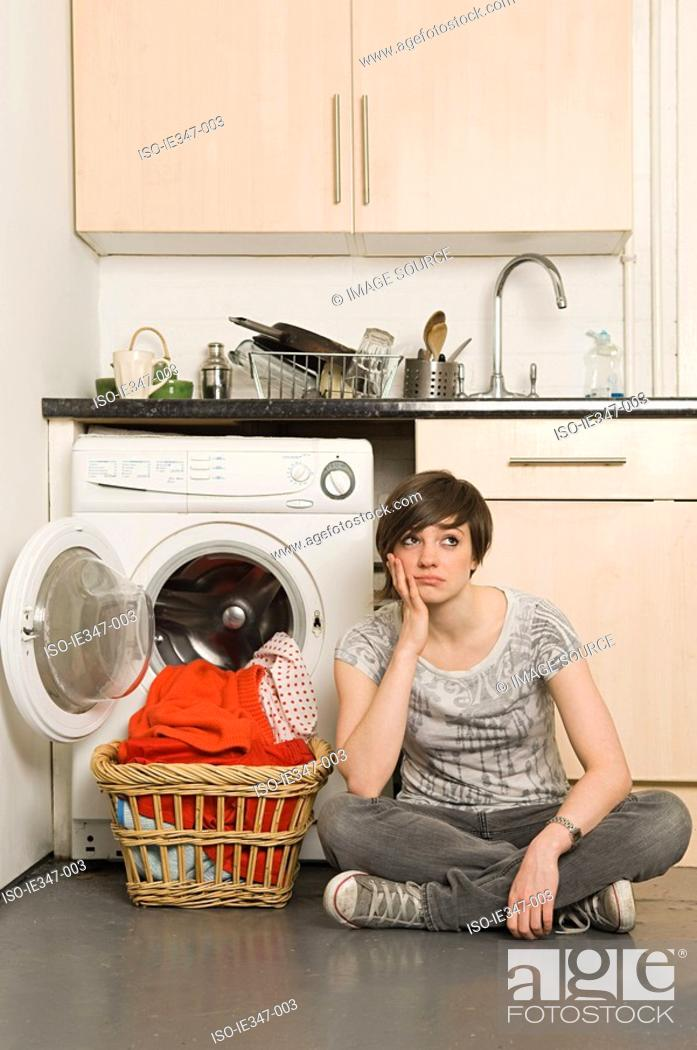 Stock Photo: Sullen young woman and laundry.