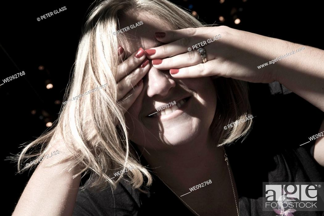 Stock Photo: Young woman covering her eyes.