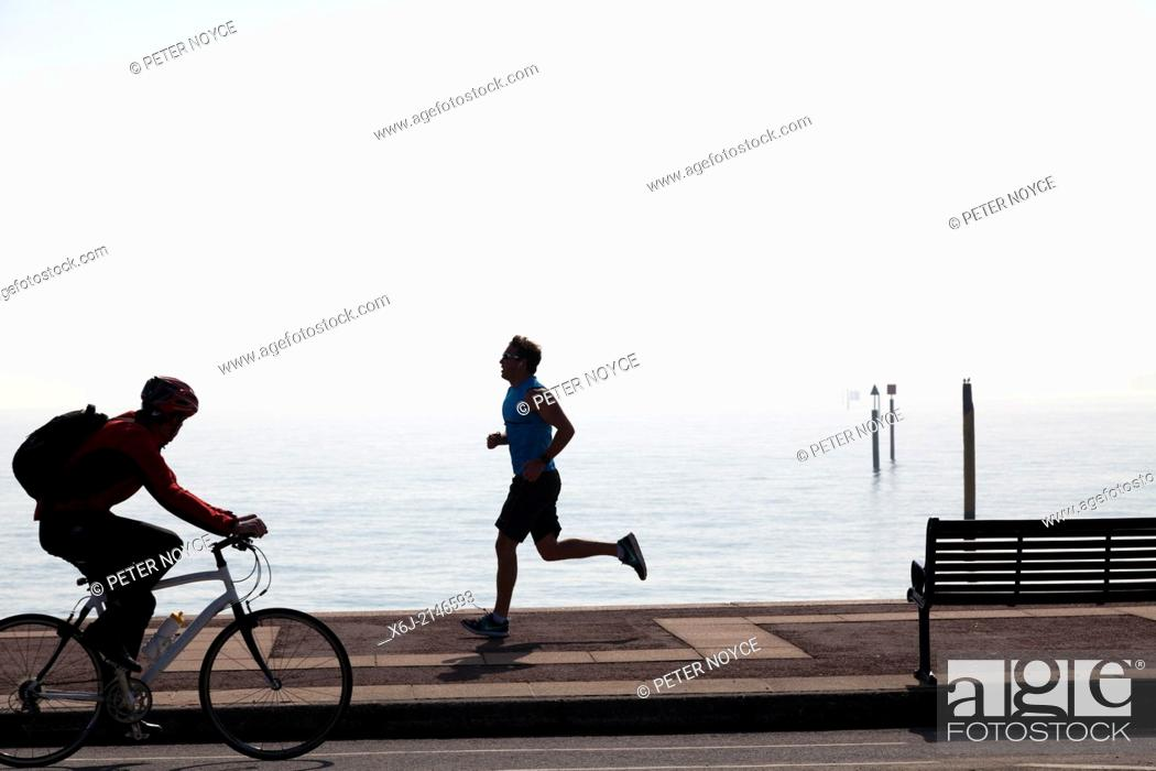 Stock Photo: Cyclist and jogger on Southsea Promenade.