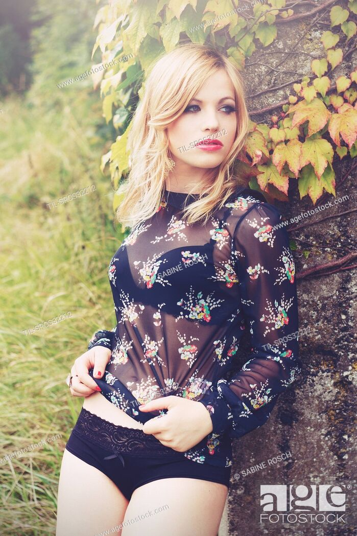 Stock Photo: young woman standing outdoor in the nature with blonde hair turning her face to the side .wearing a black underwear.