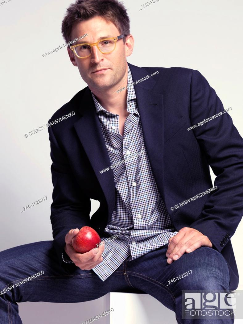 Stock Photo: Fashionably dressed man in his thirties wearing jeans and a stylish jacket holding an apple in his hand.