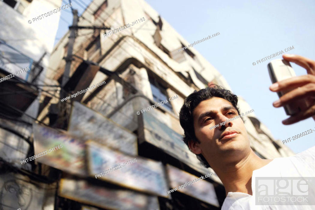 Stock Photo: Low angle view of a young man using a mobile phone.