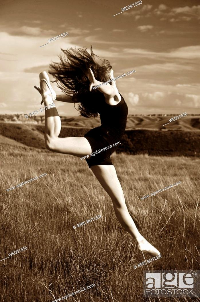 Stock Photo: Ballerina jumping in a field.
