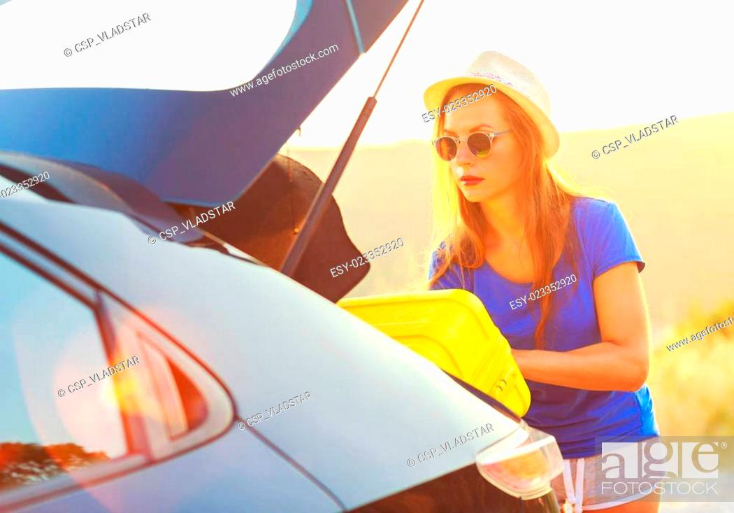 Stock Photo: Woman loading luggage into the back of car parked alongside the road.