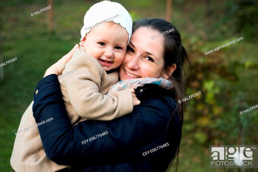 Stock Photo: Beautiful young mother carrying her cute daughter in her arms wearing warm clothes. On a walk outside in colorful autumn nature.