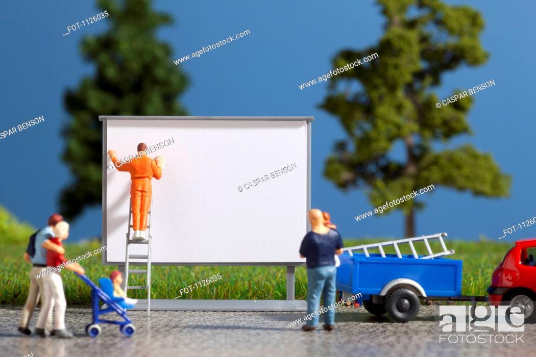 Stock Photo: A diorama of a miniature worker billboard posting.