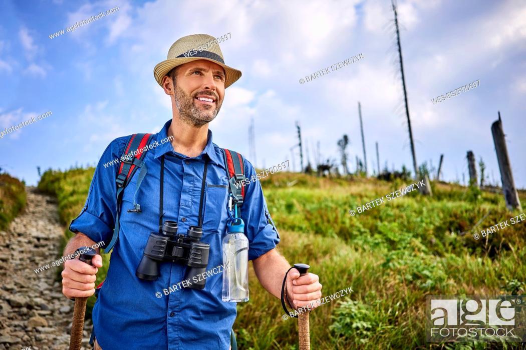 Imagen: Smiling man with binoculars hiking in the mountains.