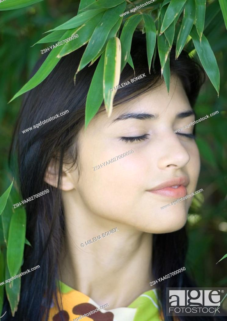 Stock Photo: Woman standing amongst leaves, head and shoulders.