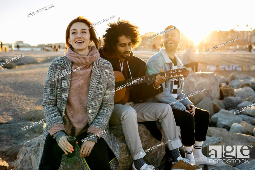 Stock Photo: Three happy friends with guitar sitting outdoors at sunset.