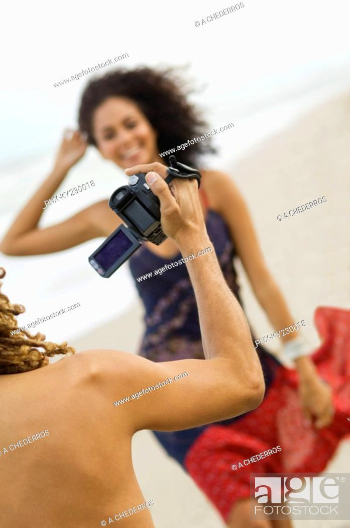 Stock Photo: Man making a video of a woman on the beach.