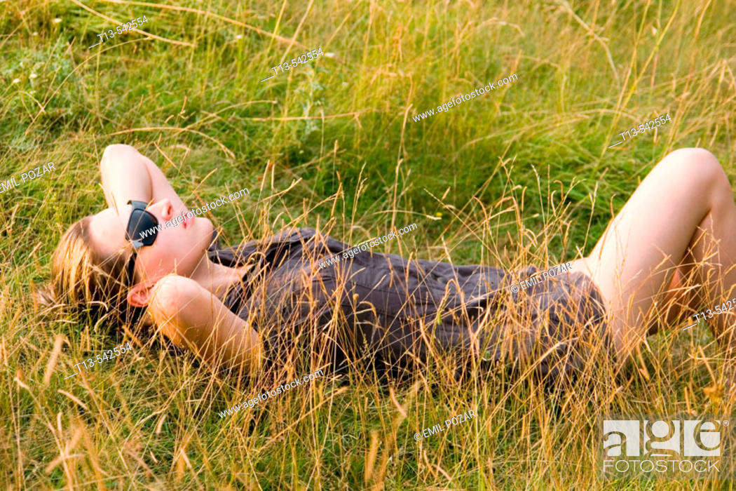 Stock Photo: Pretty young woman lying and resting in grass.